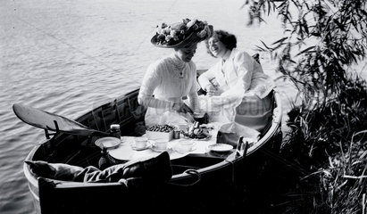 Enjoying a picnic in a rowing boat  c 1910s.