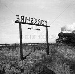 Train approaching a 'Yorkshire' sign on the boundary with County Durham  1951.