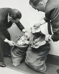 Police with sacks of money  Great Train Robbery  London  11 December 1963.