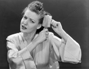 Woman brushing her hair  1940-1955.