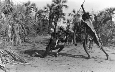 Two African tribesmen engaged in a duel wit