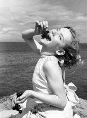 Girl eating cherries by the sea  c 1920s.