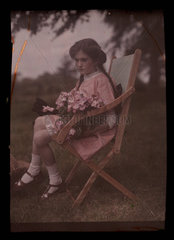Girl sitting in a chair holding flowers  1908.