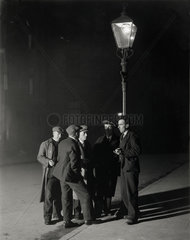 A group of unemployed men gathered round a streetlight  3 November 1931.