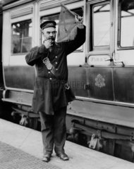 A guard at Holyhead station platform  c 1905.
