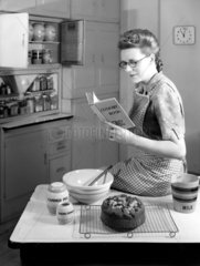 Woman reading a recipe book in a kitchen  c 1950.