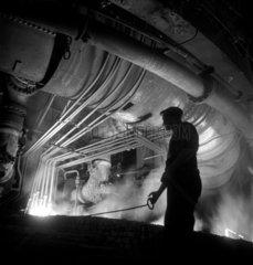 Steelworker silhouetted against blast furnace  United Steel   1947.