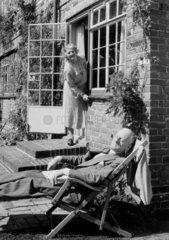 Woman calling to an elderly man asleep in a deckchair  1953.