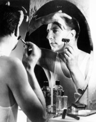 Man shaving in front of a mirror  1940s.