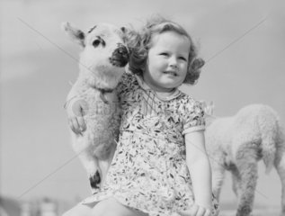 Young girl cuddingl a lamb.