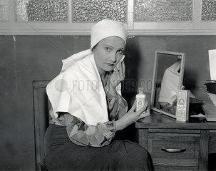 A woman using Larola face cream  30 October 1931.