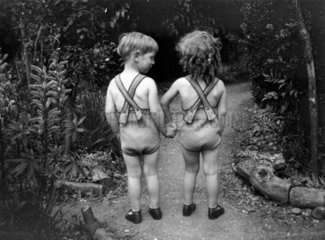 Young boy and girl wearing identical swimming costumes  c 1930s.