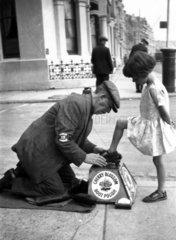 Itinerant shoeblack polishing a young girl'
