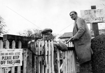 Farmer with gun sitting by 'Be Off or Be Shot' sign  30 November 1967.