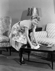 Woman polishing the coffee table  1950.