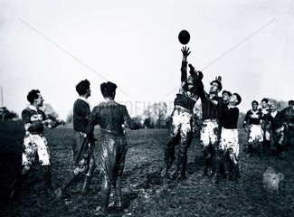 Rugby players jumping for the ball during a line-out  c 1920s.