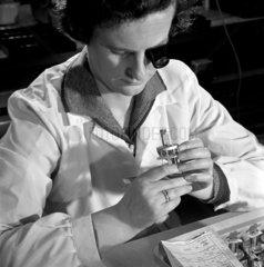 A female checker with eyeglass examines transmission valves  Mullard.