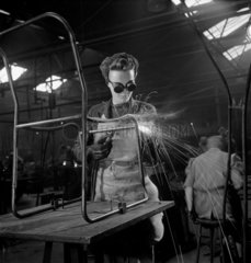 Female welder working on PEL steel and canvas chair  1948.