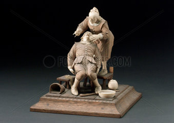 Wood and ivory figure group depicting a tooth extraction  17th century?