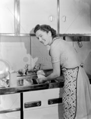 Woman washing clothes by hand in a kitchen sink  1950.