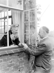 Elderly couple greeting one another at a window  1950