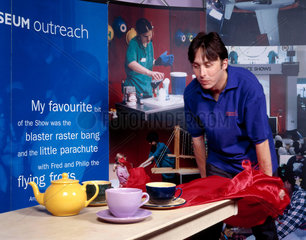 Pulling a tablecloth out from under a tea set  Science Museum  August 2001.