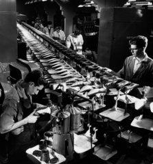 Long shot of men on Norvic Shoes production belt  checking output. 1961.
