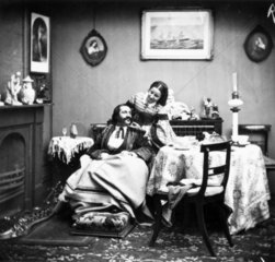 Wife caring for her invalid husband  c 1860s.