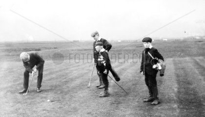 Golfer putting on a green  c 1930s. Two boy