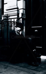 Sleeping vagrant sitting on a box in a doorway  c 1900.