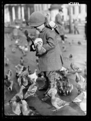 Child with pigeons in Trafalgar Square  London  7 December 1934.