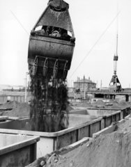Crane grab discharging coal into a rail wag