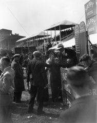 Bookmaker at a racetrack taking a bet from a gambler  c 1930s.