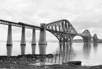 A passenger train crosses the Forth Bridge