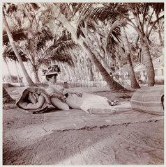 Woman lying beneath palm trees  c 1911.