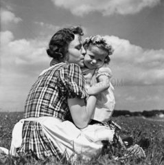 Mother kissing her child in a field  c 1930s.
