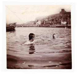 Two boys swimming in Whitby Harbour  North Yorkshire  c 1902.