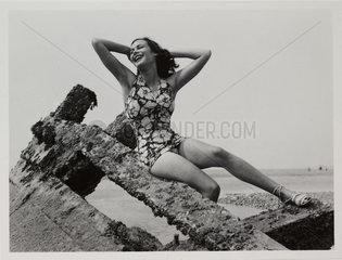 Woman posing in swimsuit on a breakwater  c 1940.