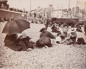 Families on beach  c 1900.
