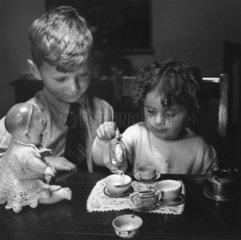 Little girl pouring tea as her brother looks on  c 1930s.