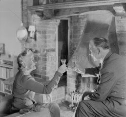 Elderly couple drinking a toast in front of a fire  1950.