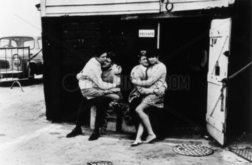 Two young couples seated outside a beach hut/garage  1967.