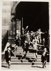 Schoolboys gleefully rushing out of school  c 1945.