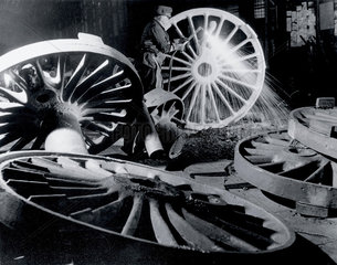 Burning off the 'runners' from driving wheel castings 1950.