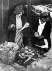 Greengrocer cleaning soil off parsnips  13 January 1945.