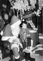 Child sitting on Father Christmas' knee  Hamleys toy shop  London  1986.