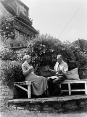 Elderly couple winding wool in the garden  1956.
