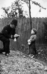 Policeman 'arresting' a small boy for scrumping apples  c 1915.