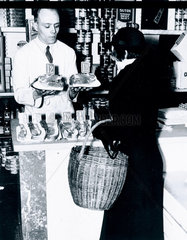 Woman choosing a side of bacon at the grocers  15 April 1937.