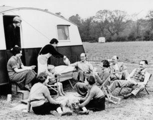 Camping Club member realxing outside caravan  c 1950s.